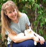 Kathy, the author, is holding her black and white cat named Bubba who taught Kathy how to assist feed him.